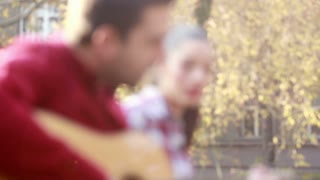 Side view of beautiful young couple singing and playing guitar in park, graded