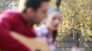 Side view of beautiful young couple singing and playing guitar in park
