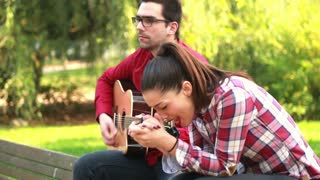 Side view of beautiful young couple sitting on park bench, man playing guitar while woman singing, graded
