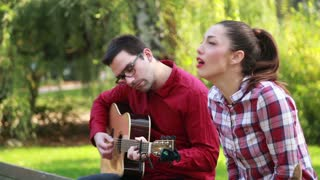 Side view of beautiful young couple sitting on park bench, man playing guitar while woman singing