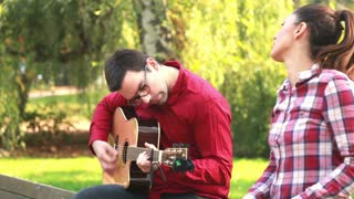 Side view of handsome man playing guitar while beautiful young woman singing, sitting next to him on bench in park, graded