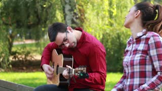 Side view of handsome man playing guitar while beautiful young woman singing, sitting next to him on bench in park