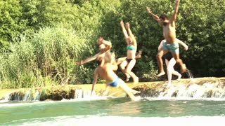 Side view of happy young friends jumping into river on beautiful sunny day, graded, in slow motion