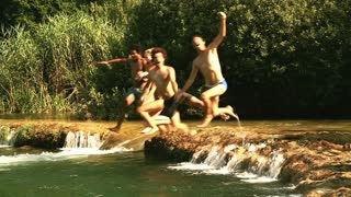 Side view of happy young friends jumping into river on beautiful sunny day, graded