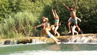 Side view of happy young friends jumping into river on beautiful sunny day, in slow motion