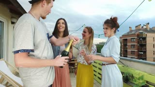 Side view of hipster man opening champagne, female friends waiting with glasses