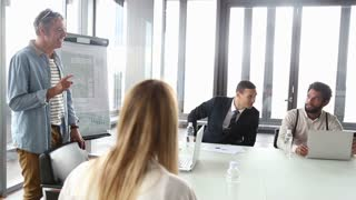 Side view of middle age creative director discussing on a meeting with colleagues in conference glass room