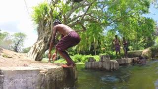 SIGIRIYA, SRI LANKA - MARCH 2014: Young boy doing a backward somersault into river.