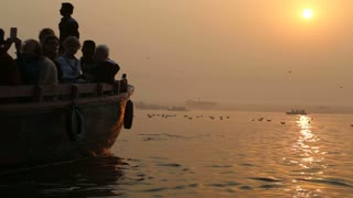 Silhouette of man rowing down the Ganges at sunset, with birds above water.