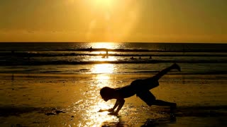 silhouetted young man doing exercises on beach at sunset in Bali