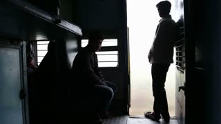 Silhouettes of men in train hall by open door during a train ride.