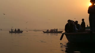 Silhouettes of people sailing in boats at Ganges at sunset.