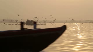 Silhouettes of people sailing in boats on the Ganges at sunset.