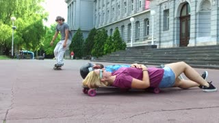 Skateboarder jumping over friends in the city street