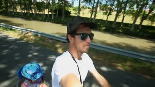 Slow motion - Man cycling with kid in bike seat