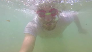 Slow motion of caucasian man diving in sea.