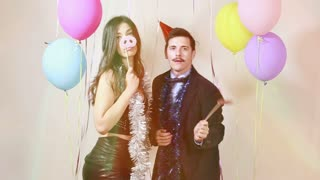 Slow motion of fun crazy couple playing with props in photo booth