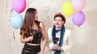 Slow motion of funny crazy couple in love having fun in photo booth