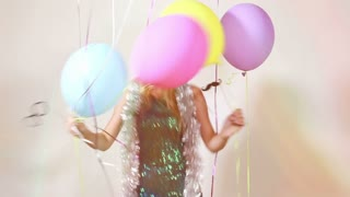 Slow motion of happy blonde woman jumping with balloons in photo booth