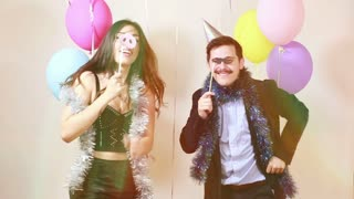 Slow motion of happy crazy couple enjoying in photo booth