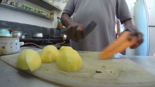 Slow motion of man slicing carrots and potatoes with a knife in kitchen.