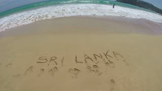 Slow motion of view of waves washing onto beach over writing in the sand Sri Lanka