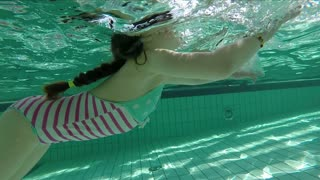 Slow motion of young girl swimming underwater with goggles