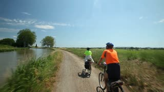 Slow motion - Retired couple cycling beside river on holiday