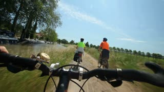 Slow motion - Retired couple cycling beside river on holidays