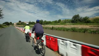 Slow motion - Retired couple cycling on road beside river on holidays