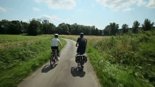 Slow motion - Retired couple cycling on road in village in France
