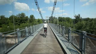 Slow motion - Woman cycling on road over suspension bridge