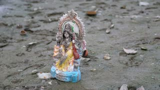 Small statue of Shiva on dirty shore of Ganges, with people in background.