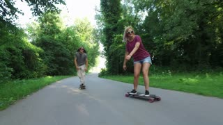 Smiling blonde woman longboarding with friends