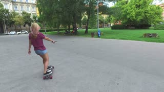 Smiling blonde woman on a longboard in the city park