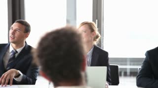 Smiling business people sitting at table on a meeting in conference room, listening presentation