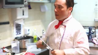 Smiling chef sharpening knives