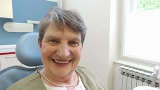 Smiling elderly female patient at dentist