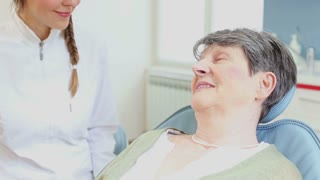 Smiling elderly woman talking with dentist