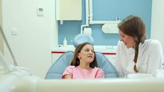 Smiling female dentist talking with lovely little girl