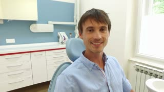 Smiling man with healthy white teeth at dentist