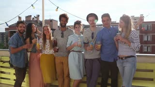 Smiling multi-ethnic friends toasting on the rooftop terrace