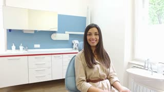 Smiling woman looking at camera while sitting in the dental chair