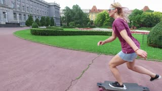 Smiling women longboarding with friends in the city