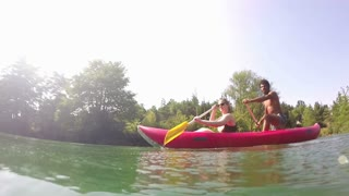 Split shot of a cute young couple looking at camera while paddling canoe on beautiful summer day, graded, in slow motion