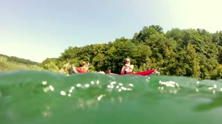 Split shot of four young friends having fun in a canoe on beautiful summer day, graded, in slow motion