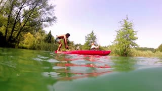 Split shot of handsome young man doing backflip from a canoe into water while girl paddling canoe, graded, in slow motion