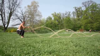 Sports man is training with ropes