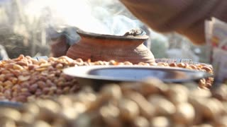 Steam coming out of jar surrounded by pile of Indian nuts.