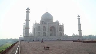 Taj Mahal front view from outdoor patio, with people passing.